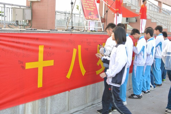 """东莞市 成人/最后,全体学生在""""十八岁 与梦想同行""""的横幅中签上自己的名字..."""